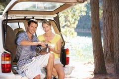 坐在汽车启动之后的新夫妇 免版税库存图片