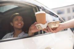 坐在汽车和买的咖啡的妇女去 免版税库存照片