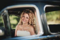 坐在汽车和微笑的新娘 库存照片