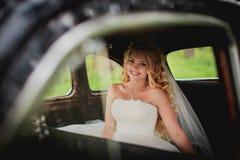 坐在汽车和微笑的新娘 免版税库存图片