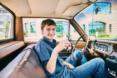 坐在汽车和把握关键的愉快的年轻人 免版税图库摄影
