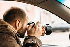 坐在汽车和拍与专业照相机的私家侦探或记者或者无固定职业的摄影师照片 免版税库存图片