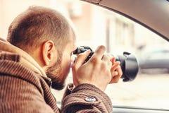 坐在汽车和拍与专业照相机的调查员或私家侦探或者记者或者无固定职业的摄影师照片 免版税库存图片