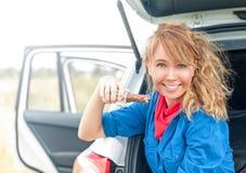 坐在汽车和拿着巧克力的愉快的女孩。 图库摄影