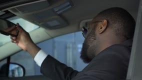 坐在汽车和看在后视镜,严肃的交涉,黑手党的男性 股票录像