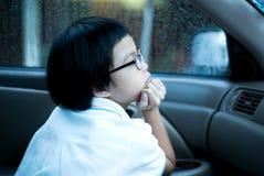 坐在汽车和看在窗口外面的画象亚裔女孩观看雨 图库摄影