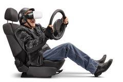 坐在汽车座位和使用VR耳机的年长骑自行车的人 免版税库存图片