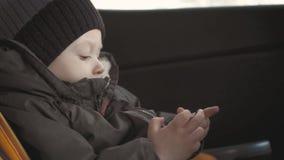 坐在汽车座位和观看从智能手机的逗人喜爱的小孩男婴录影 使用在有智能手机的汽车的孩子 股票视频