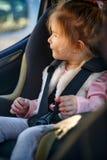 坐在汽车座位的逗人喜爱的女孩-安全保卫 库存照片