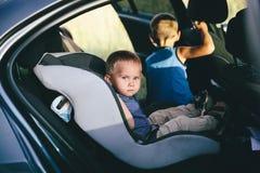 坐在汽车座位的逗人喜爱的小孩男孩画象  r 库存照片