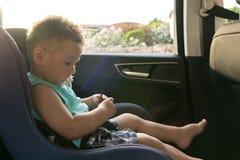 坐在汽车座位的逗人喜爱的小孩男孩画象  儿童运输安全 免版税库存图片