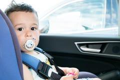 坐在汽车座位的逗人喜爱的小孩男孩画象  儿童运输安全 库存图片