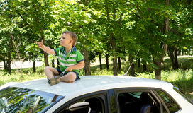 坐在汽车指向顶部的年轻白肤金发的男孩 免版税库存照片