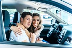 坐在汽车沙龙的愉快的异性爱夫妇,拥抱 库存图片