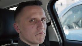 坐在汽车的一个人的画象 他指向他的手指直接地照相机 影视素材