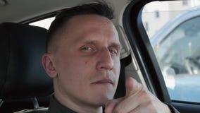 坐在汽车的一个人的画象 他指向他的手指直接地照相机 股票视频