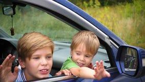 坐在汽车的两个孩子 兄弟看窗口和微笑 愉快的童年 影视素材