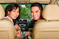 坐在汽车的亚洲夫妇 库存照片