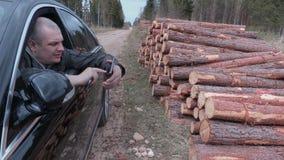 坐在汽车的伐木工人在日志堆和谈话附近 股票视频