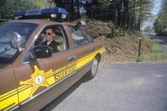 坐在汽车的县司法行政官 免版税库存图片