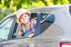 坐在汽车的可爱的小孩男孩在途中对与他的父母的暑假 库存图片