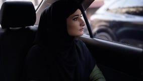 坐在汽车的后座和好奇地看在街道的黑hijab的美女,当路时 影视素材