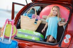 坐在汽车的后车箱的一个小女孩的画象 免版税库存图片