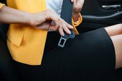 坐在汽车的女实业家投入在她的安全带 免版税库存图片