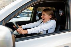 坐在汽车的害怕妇女 免版税图库摄影