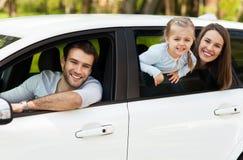 坐在汽车的家庭看窗口 免版税库存图片