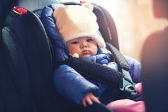 坐在汽车的小女孩在冬天穿衣 免版税库存图片