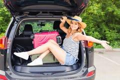 坐在汽车的开放后车箱的年轻可爱的妇女 夏天旅行 免版税库存照片