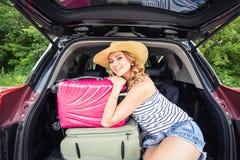 坐在汽车的开放后车箱的年轻可爱的妇女 夏天旅行 免版税库存图片