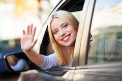 坐在汽车的微笑的少妇 免版税库存图片