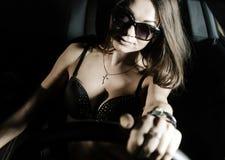 坐在汽车的性感的魅力女孩 免版税库存照片