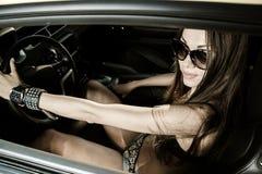 坐在汽车的性感的魅力女孩 库存图片