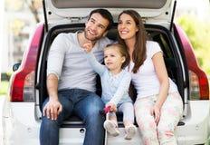 坐在汽车的愉快的家庭 免版税库存图片