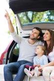 坐在汽车的愉快的家庭 库存照片