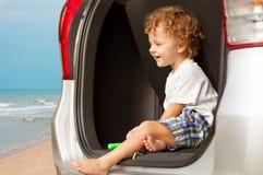 坐在汽车的愉快的小男孩 免版税库存图片