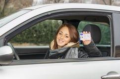 坐在汽车的愉快的年轻女人微笑对显示她的驾照的照相机 免版税库存照片