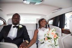 坐在汽车的新婚佳偶非洲夫妇 免版税图库摄影