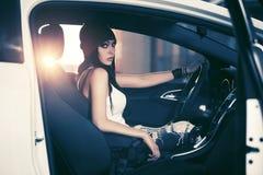 坐在汽车的无袖衫的年轻时尚妇女 免版税库存图片