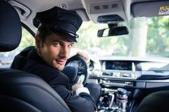 坐在汽车的男性汽车夫 免版税库存图片