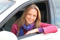 坐在汽车的白肤金发的妇女 库存图片
