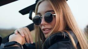 坐在汽车的确信的白肤金发的妇女 股票录像