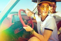 坐在汽车的笑的浪漫夫妇,当在旅行夏日时 免版税库存图片