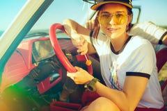 坐在汽车的笑的浪漫夫妇,当在旅行夏日时 免版税图库摄影