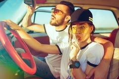 坐在汽车的笑的浪漫夫妇,当在旅行夏日时 库存图片