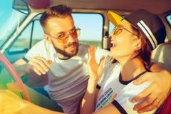 坐在汽车的笑的浪漫夫妇,当在旅行夏日时 库存照片