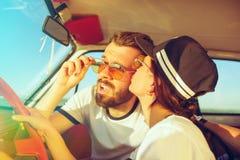 坐在汽车的笑的浪漫夫妇,当在旅行夏日时 图库摄影